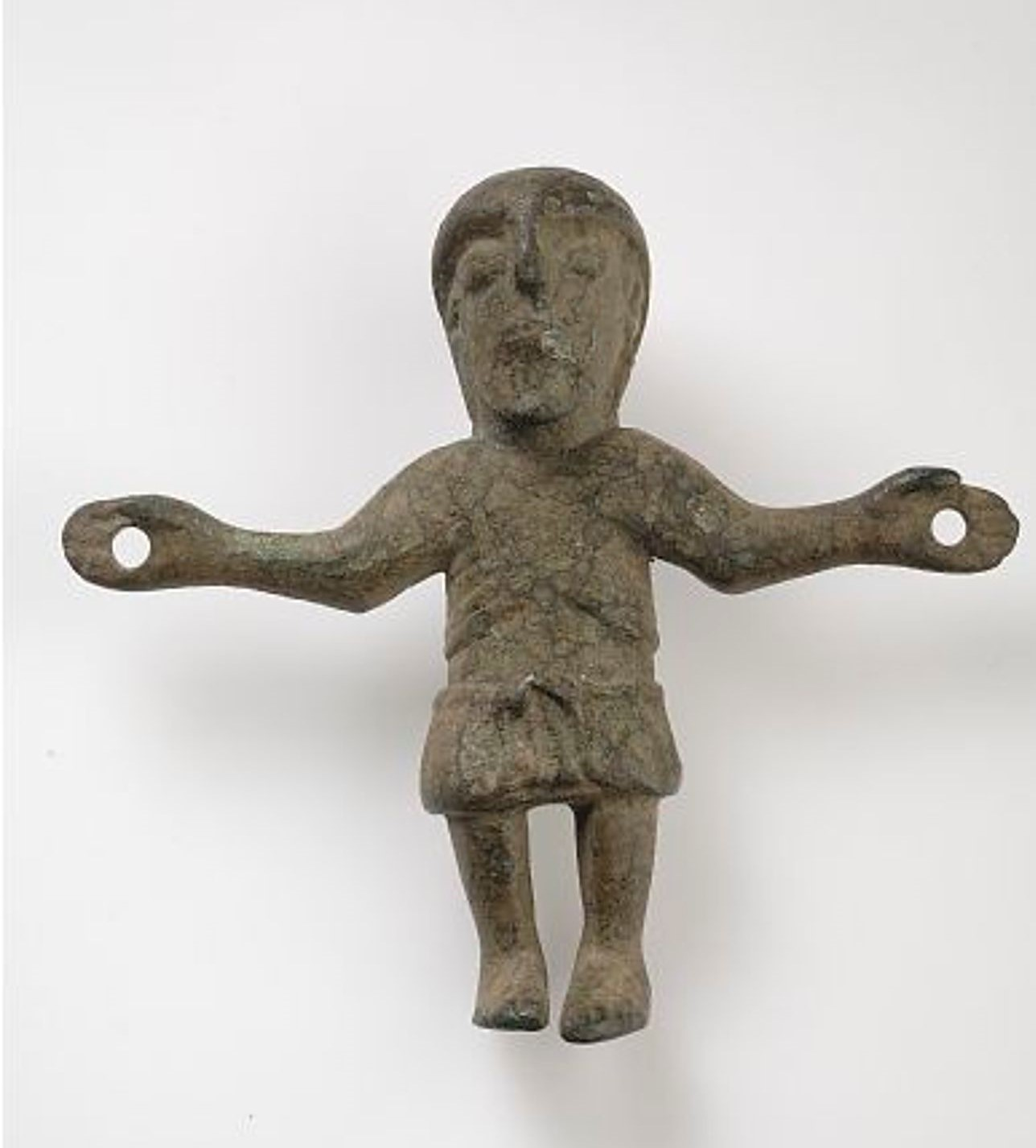 En liten bronsskulptur som föreställer Kristus på korset.