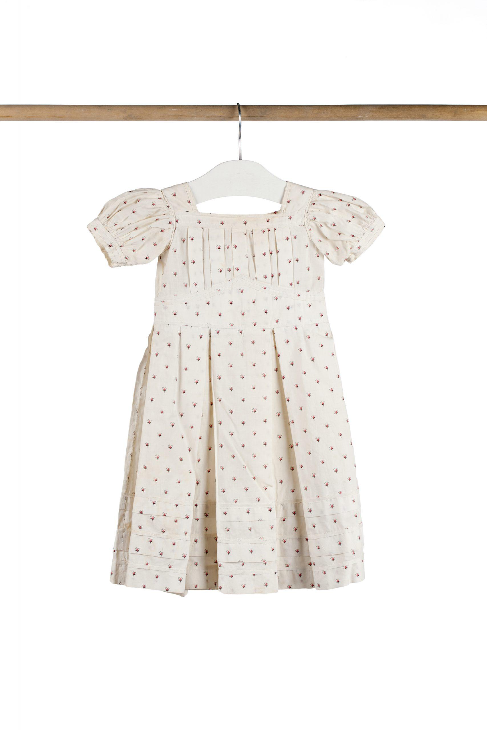 Barnklänning av vitt tyg med mönster av små ljusröda rosenknoppar.