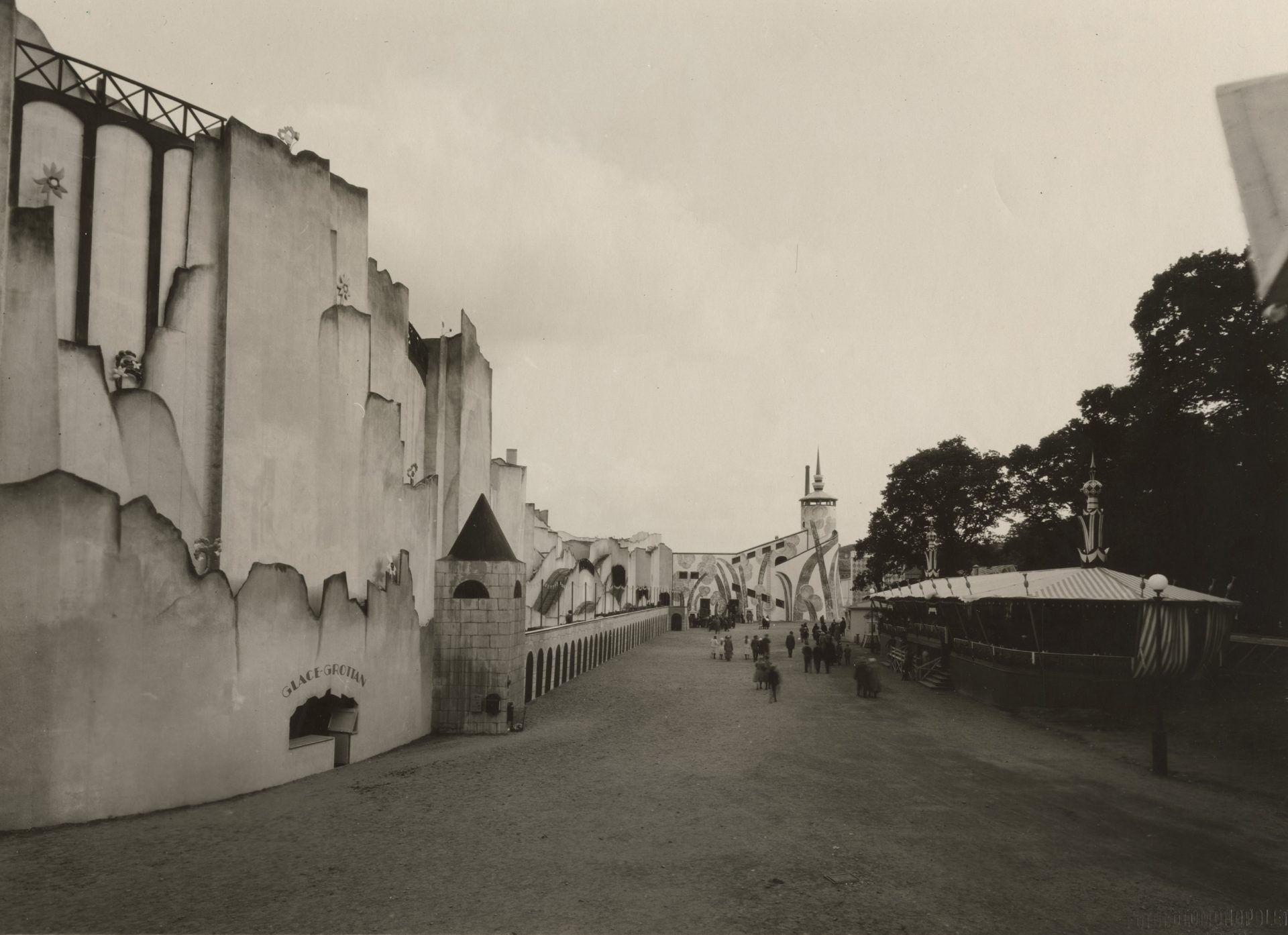 """Svartvit bild från utställningen i Göteborg 1923. I förgrunden en byggnad med skylten """"Glace-grottan""""."""