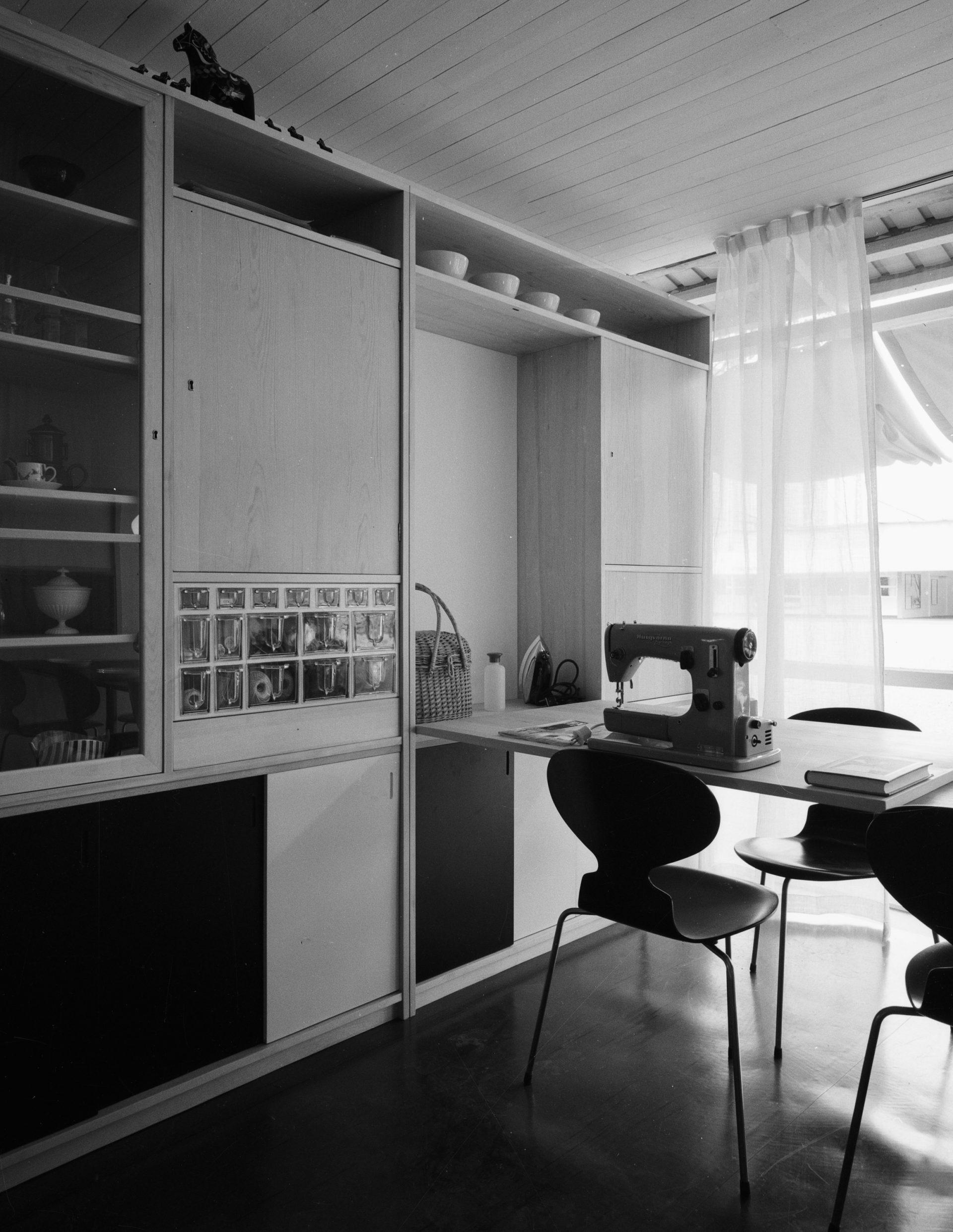 Bilden från 1955 visar ett rum med bokhylla, arbetsbord med symaskin och stolar av modellen Myran.