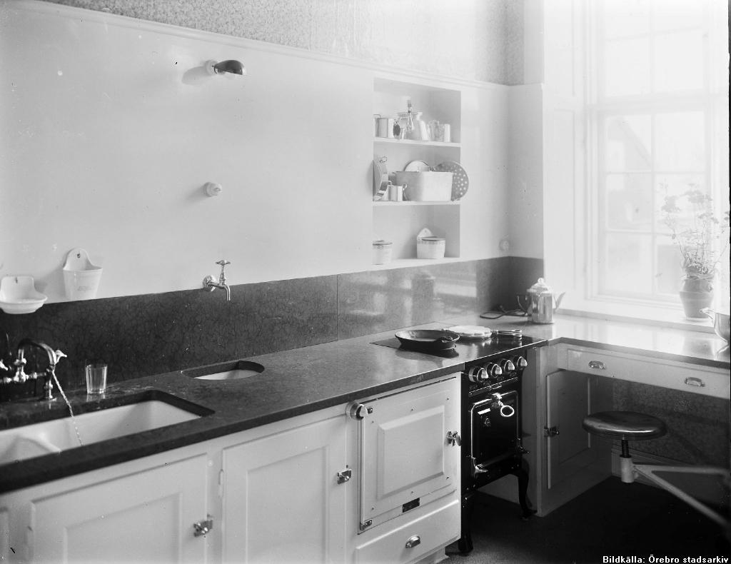 Ett kök från 1928 med vita skåpluckor, blank svart diskbänk, vedspis och diskho med rinnande vatten.