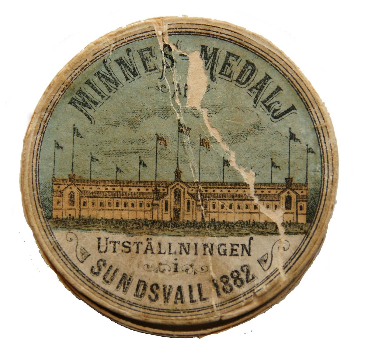 """Rund minnespenning med teckning av en byggnad med många flaggor och texten """"Minnesmedalj av utställningen i Sundsvall 1882""""."""