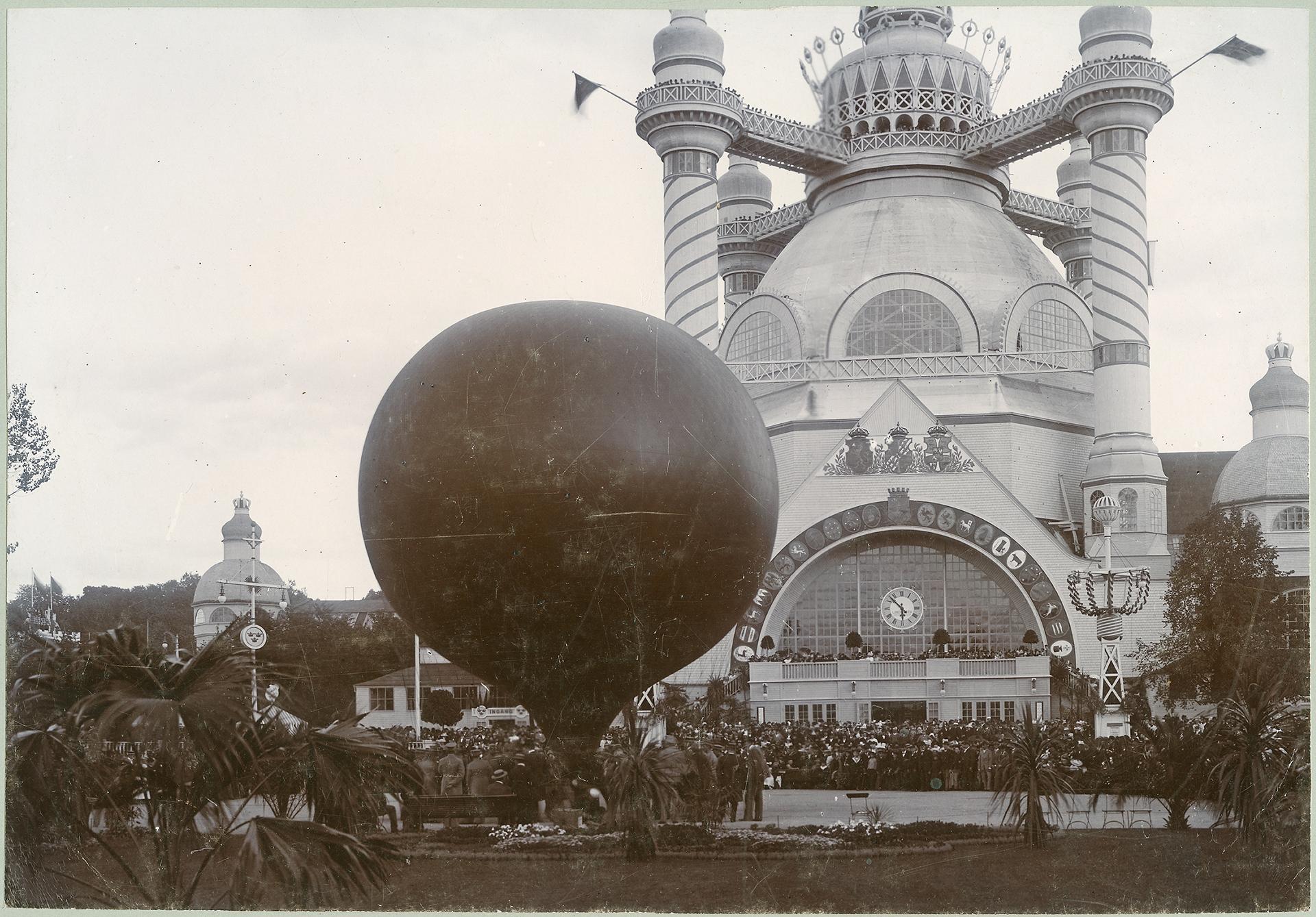 En luftballong framför den stora industrihallen. Hundratals människor står tätt tillsammans framför byggnaden och tittar mot ballongen.