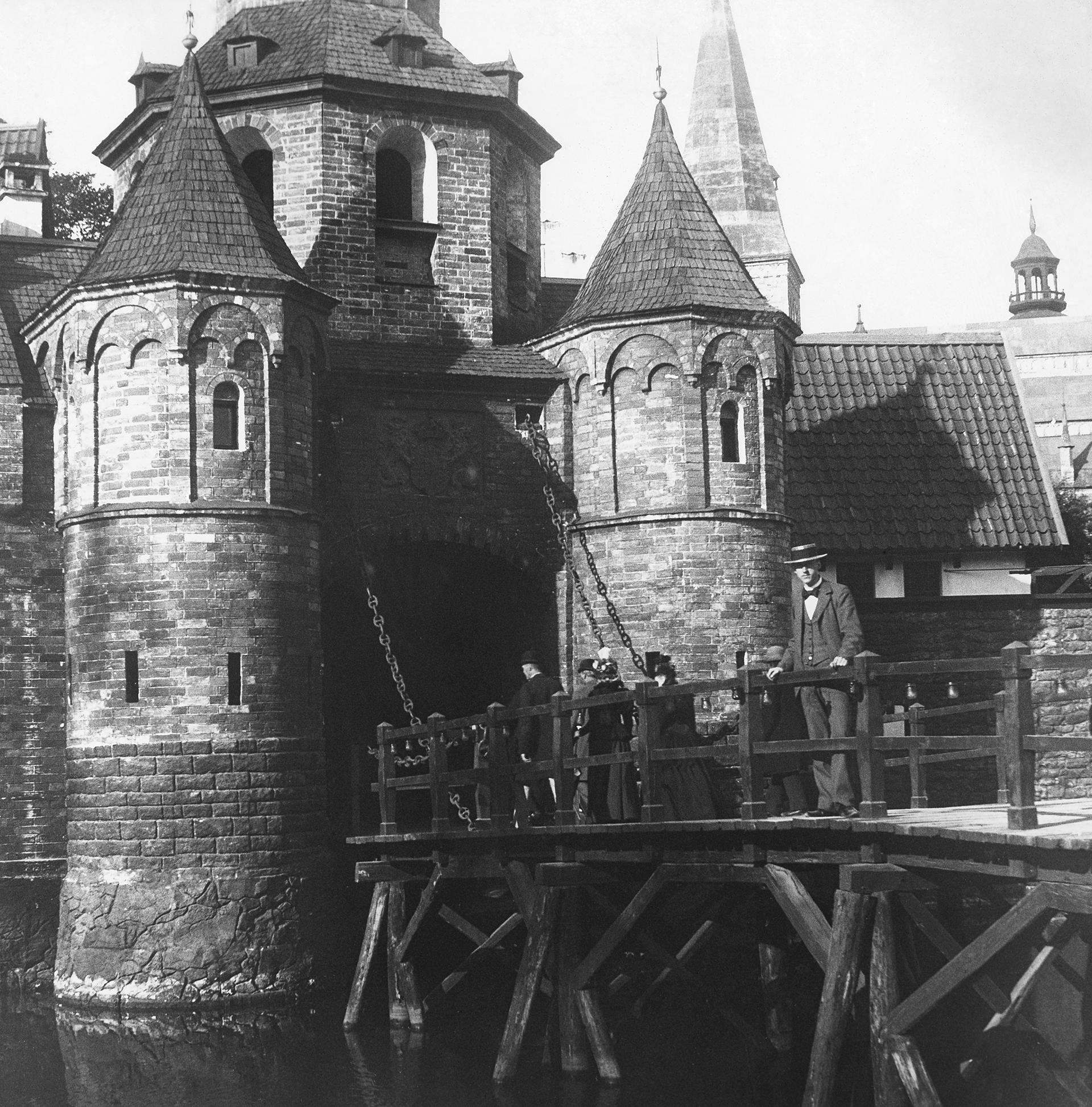 På en träbro står några människor. Bron leder till en byggnad med torn som ser medeltida ut.