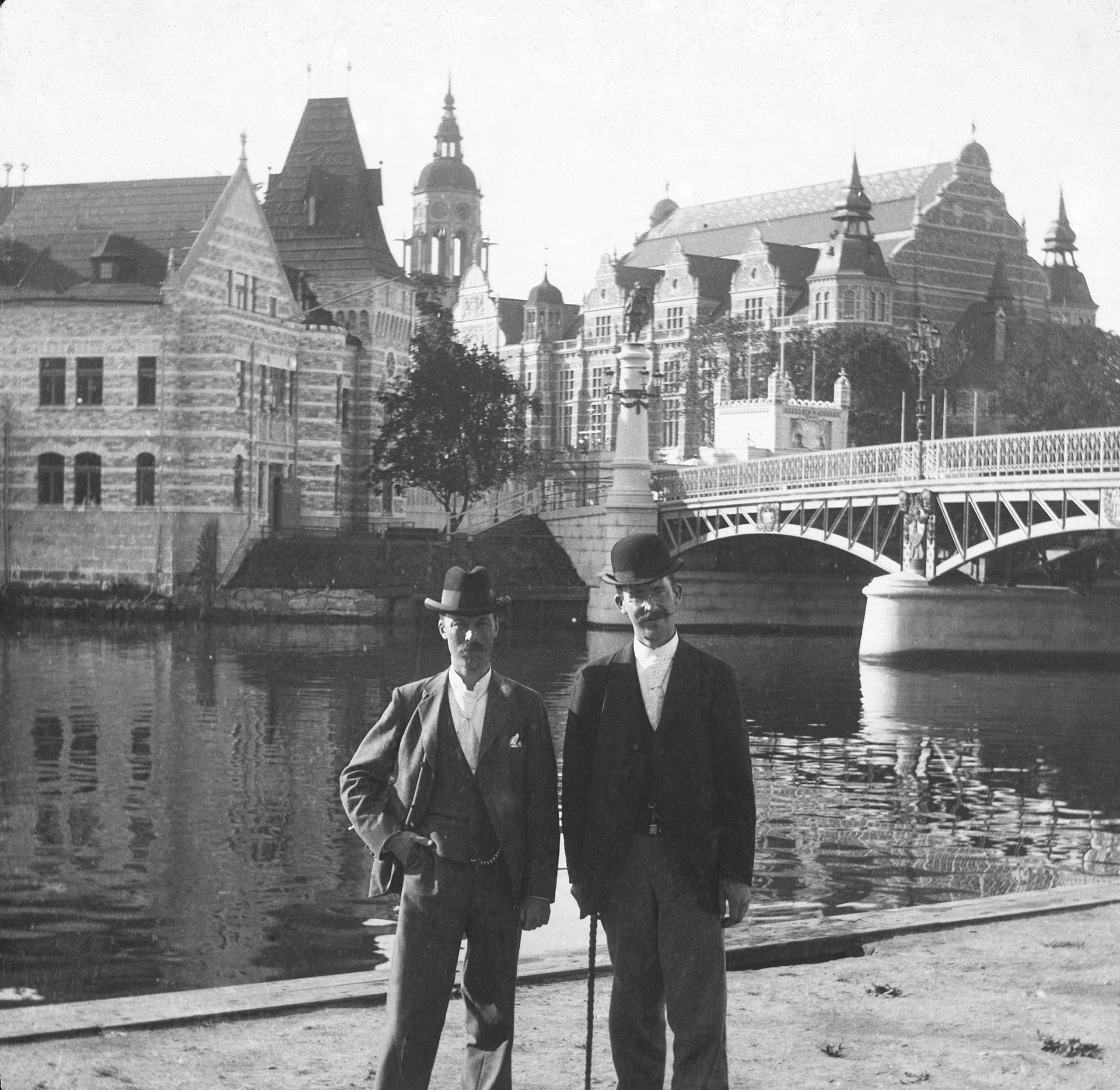 I förgrunden två män i mörka kostymer och plommonstop. I bakgrunden Djurgårdsbron och Nordiska museet.