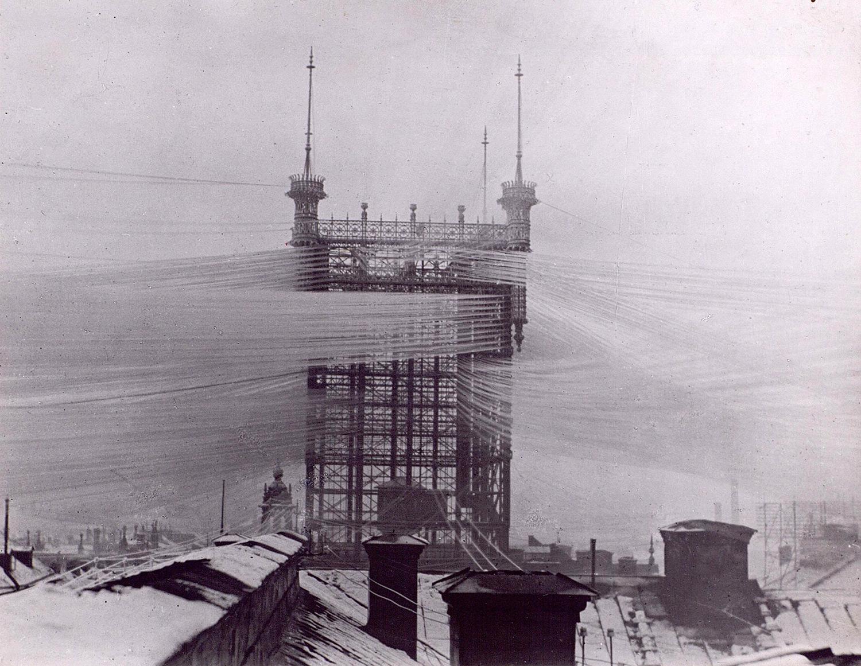 Telefontornet var byggt av metallbalkar. Det sticker upp högt över hustaken. Från toppen utgår tusentals telefonledningar.
