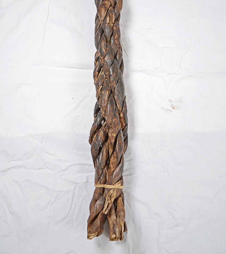Närbild på änden av ett läderrep som är flätat av flera läderband och ombundet med ett snöre.