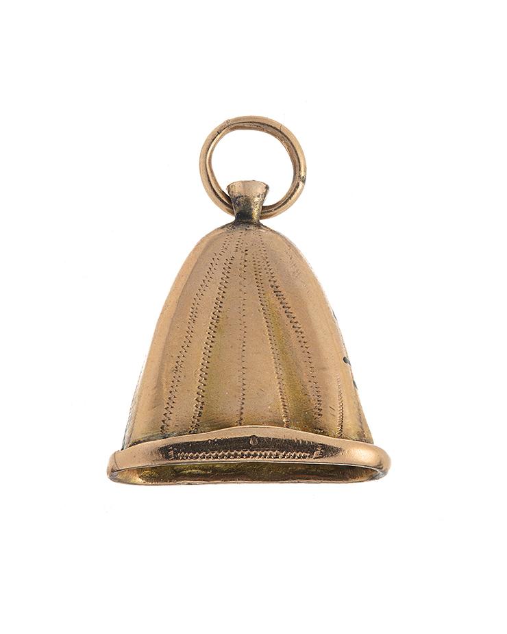 Berlocken är guldfärgad med zigzagmönster. Längst upp sitter en ring, som man kan trä en halskedja igenom.