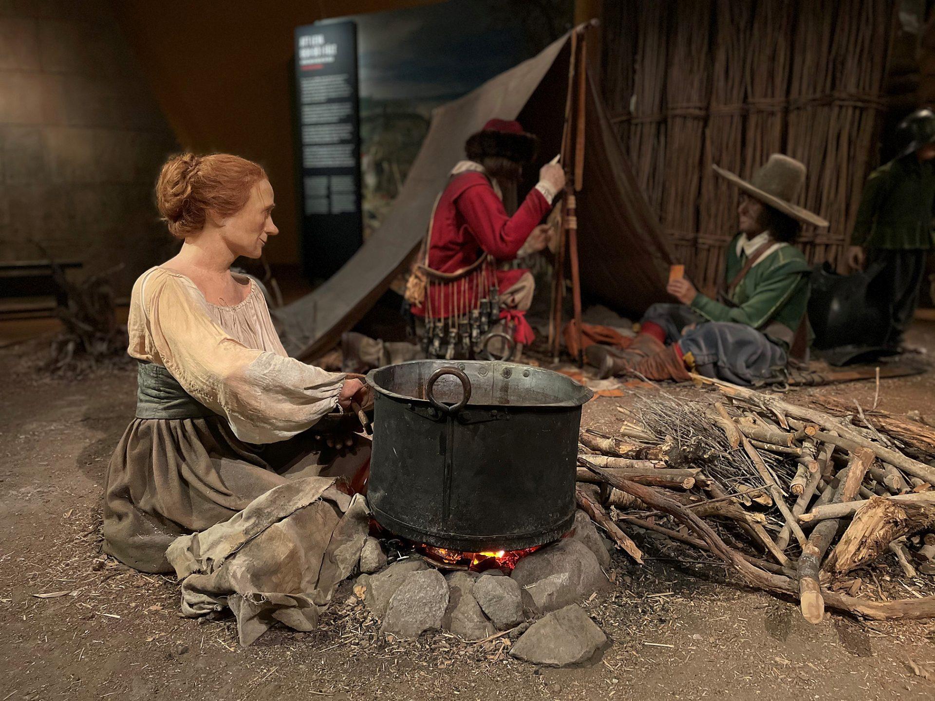 En kvinna som sitter vid en gryta över en öppen eld och två män i bakgrunden.