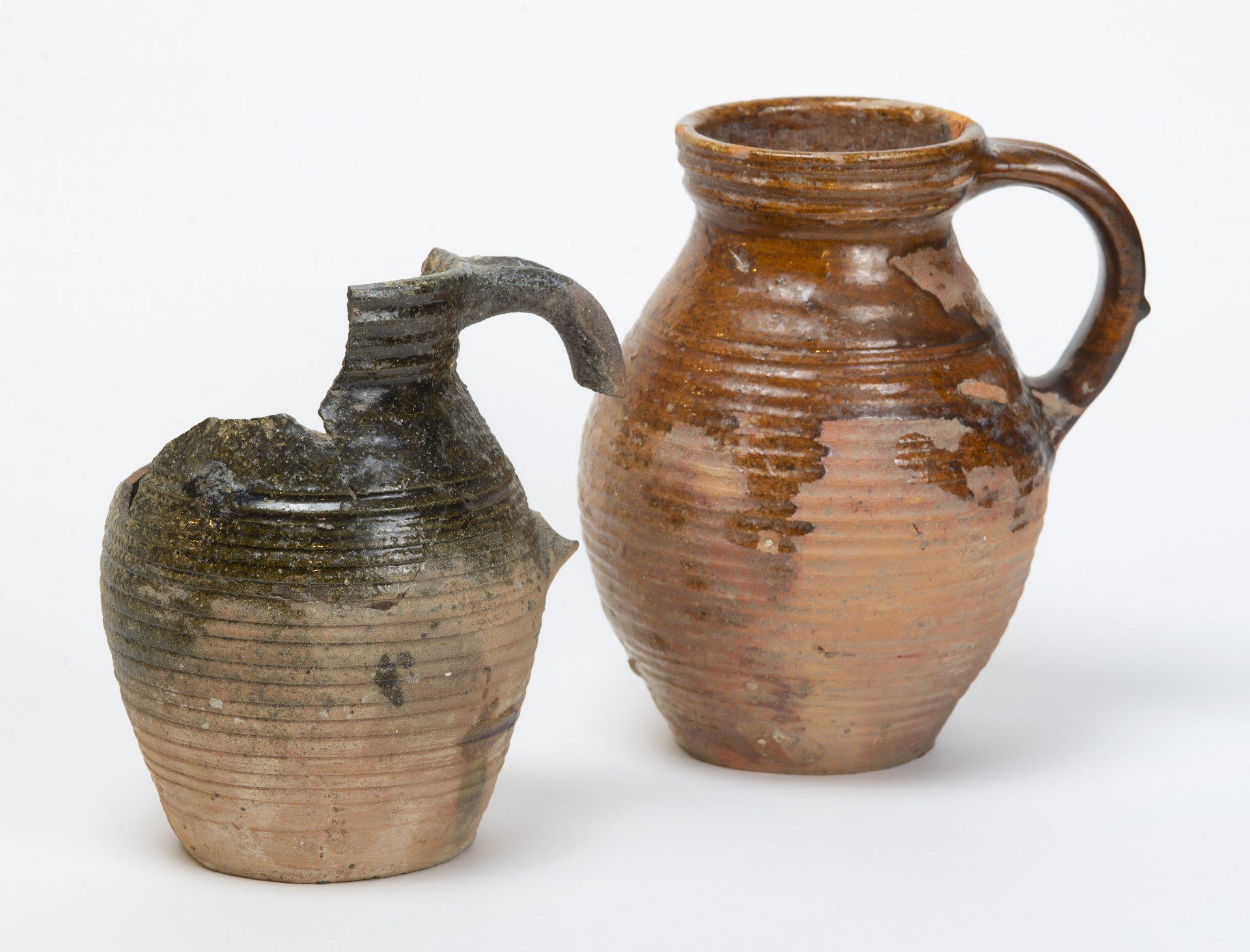 Två keramikkannor, en är trasig med svart glasyr. Den andra är hel och har brun glasyr.
