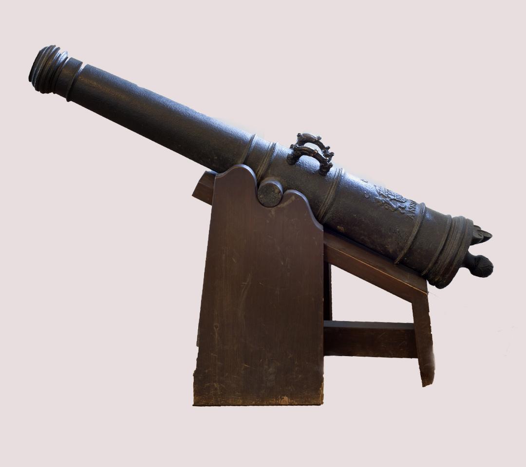 En kanon av brons på en trälavett.