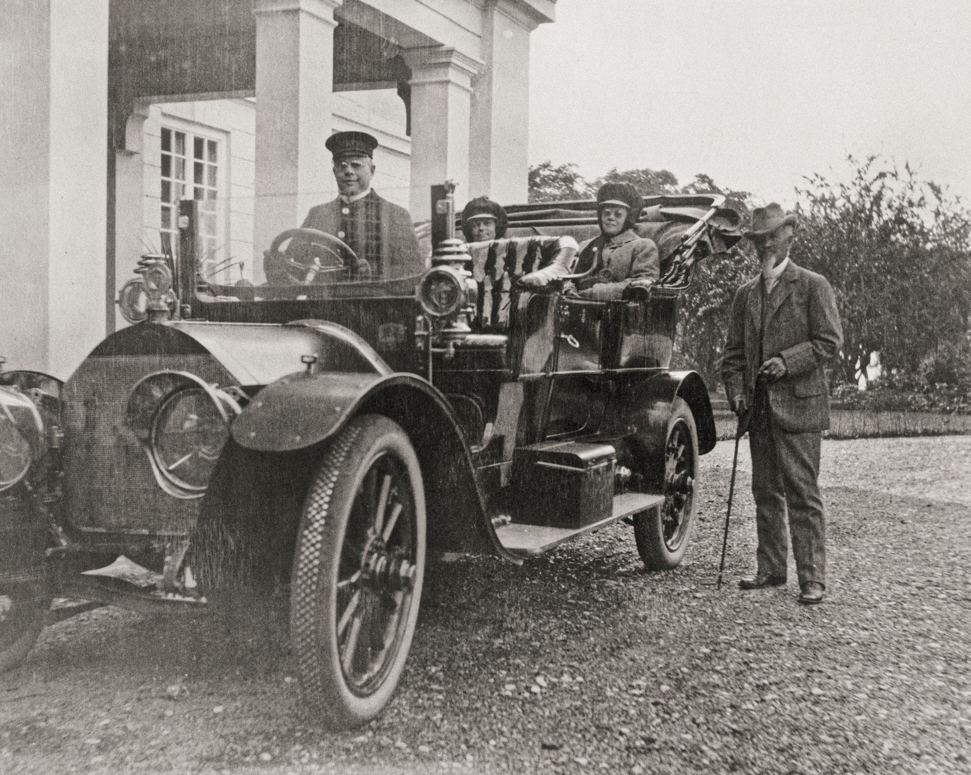 Ett gammalt foto på ett sällskap som ska ut och åka bil. I förarsätet sitter en chaufför och greve von Hallwyls står bredvid.
