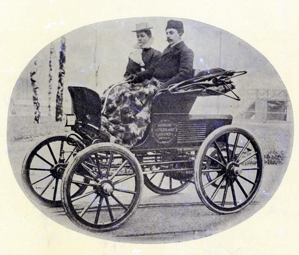 Ett gammalt svartvitt foto på ett par i en automobil.