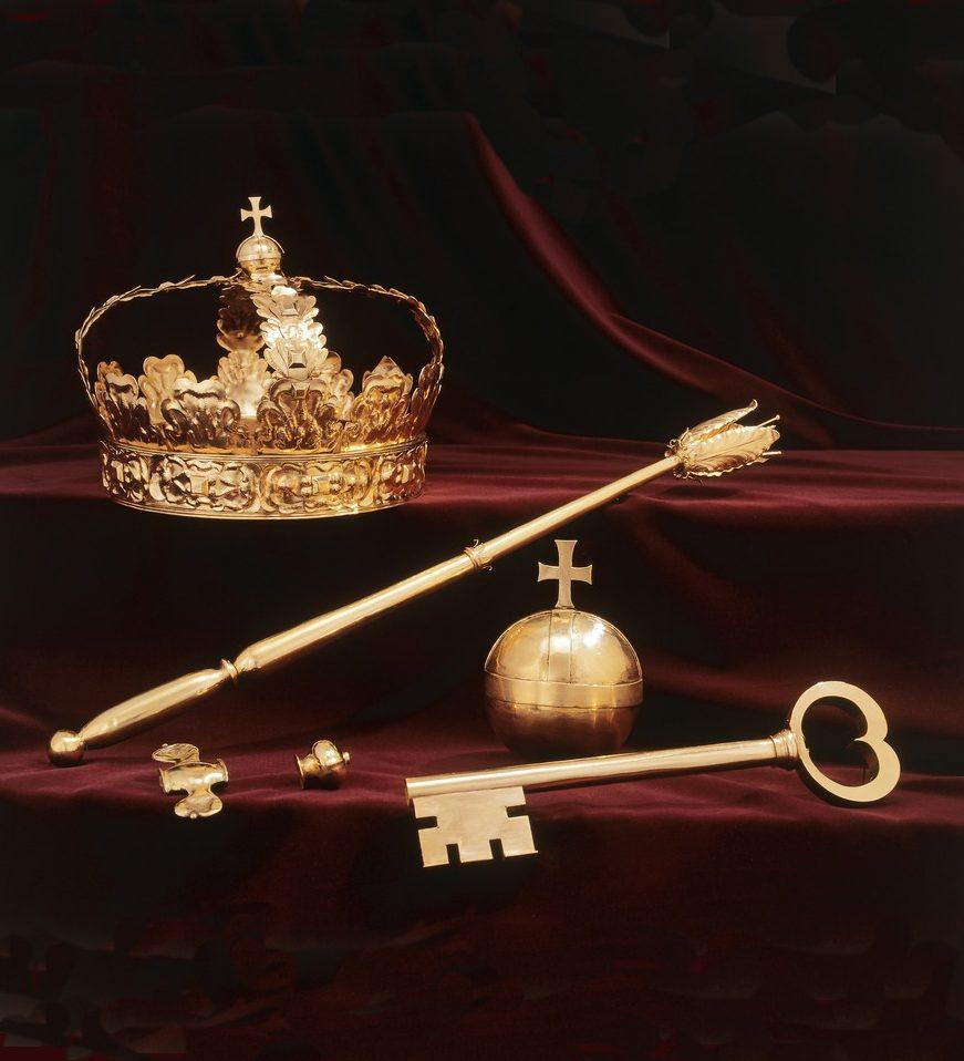 En kungakrona, en spira, en nyckel och ett äpple på ett rött sammetstyg.