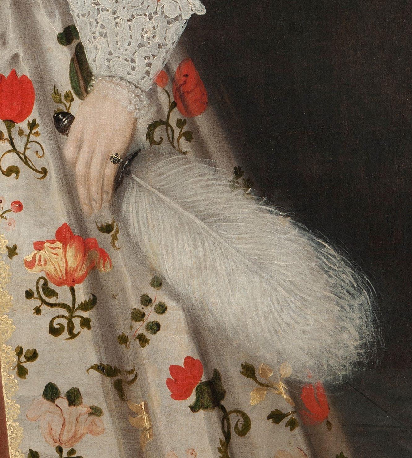 Detalj av en hand som håller i en strutsfjäder.