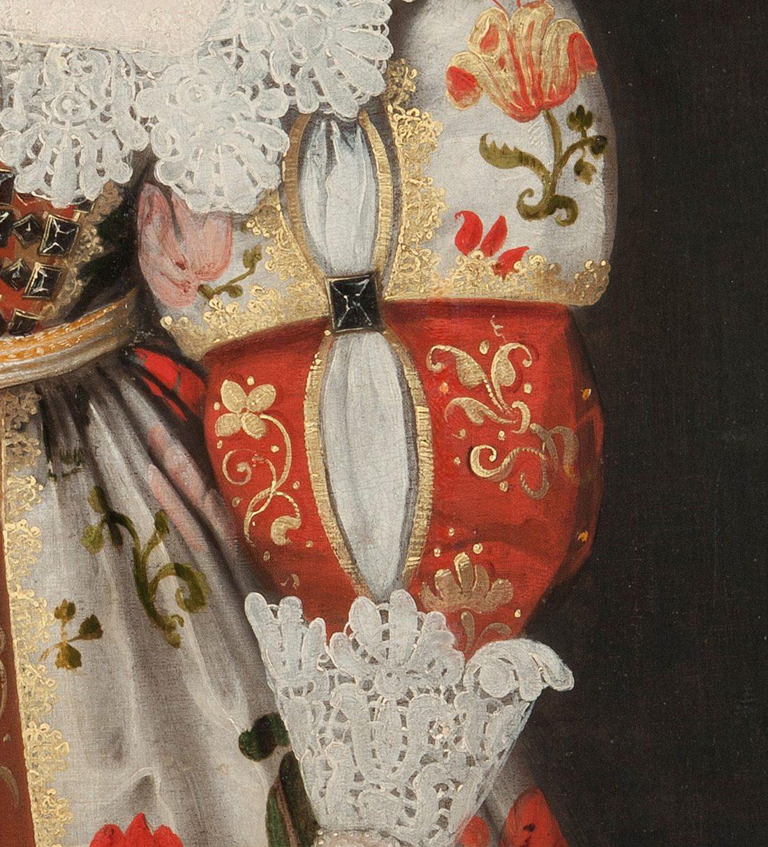 Detaljbild av ärmen, med brokiga tyger och framvällande spets.