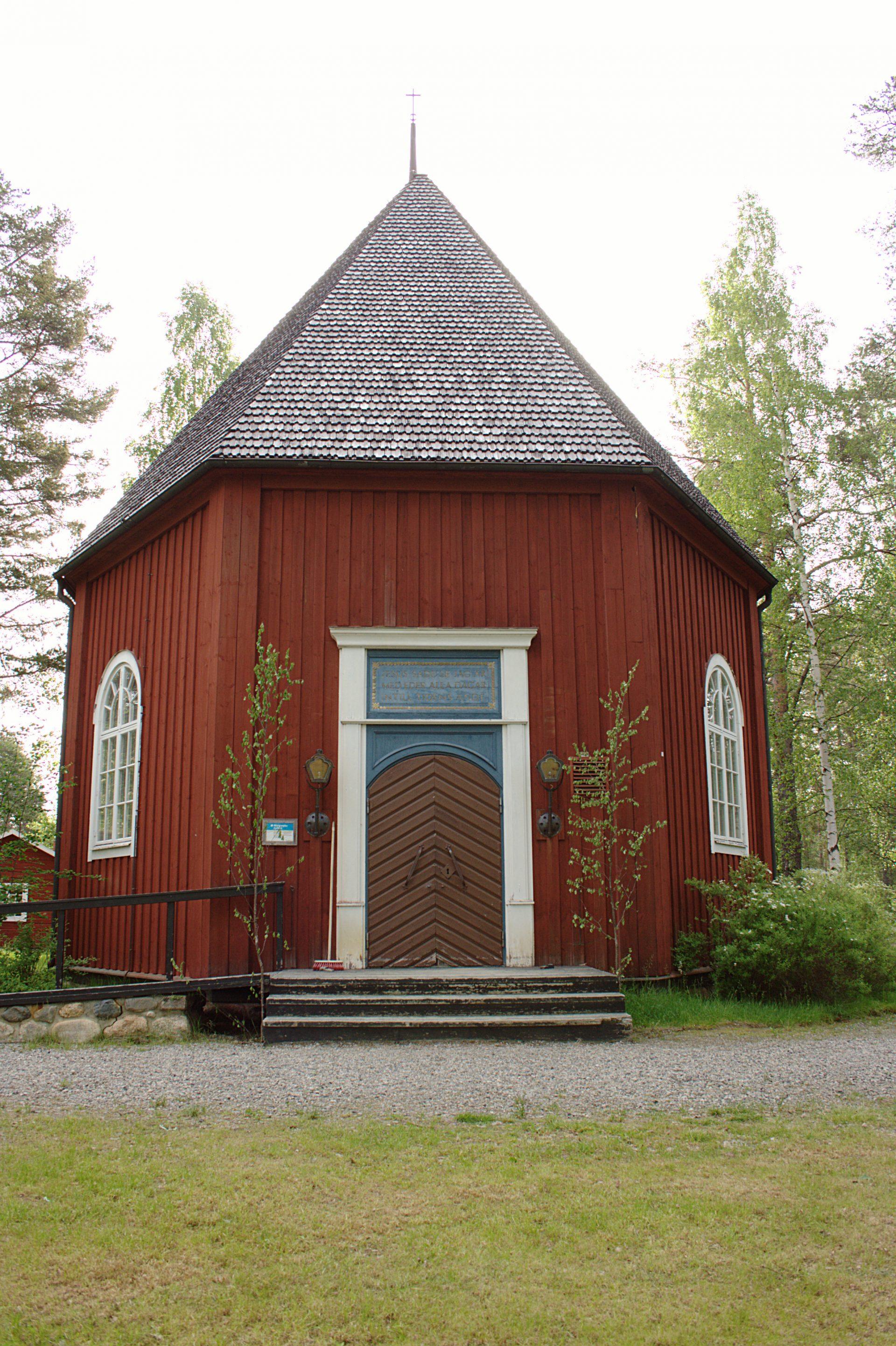 En rödmålad byggnad med spetsigt tak och vita dörr- och fönsterposter.