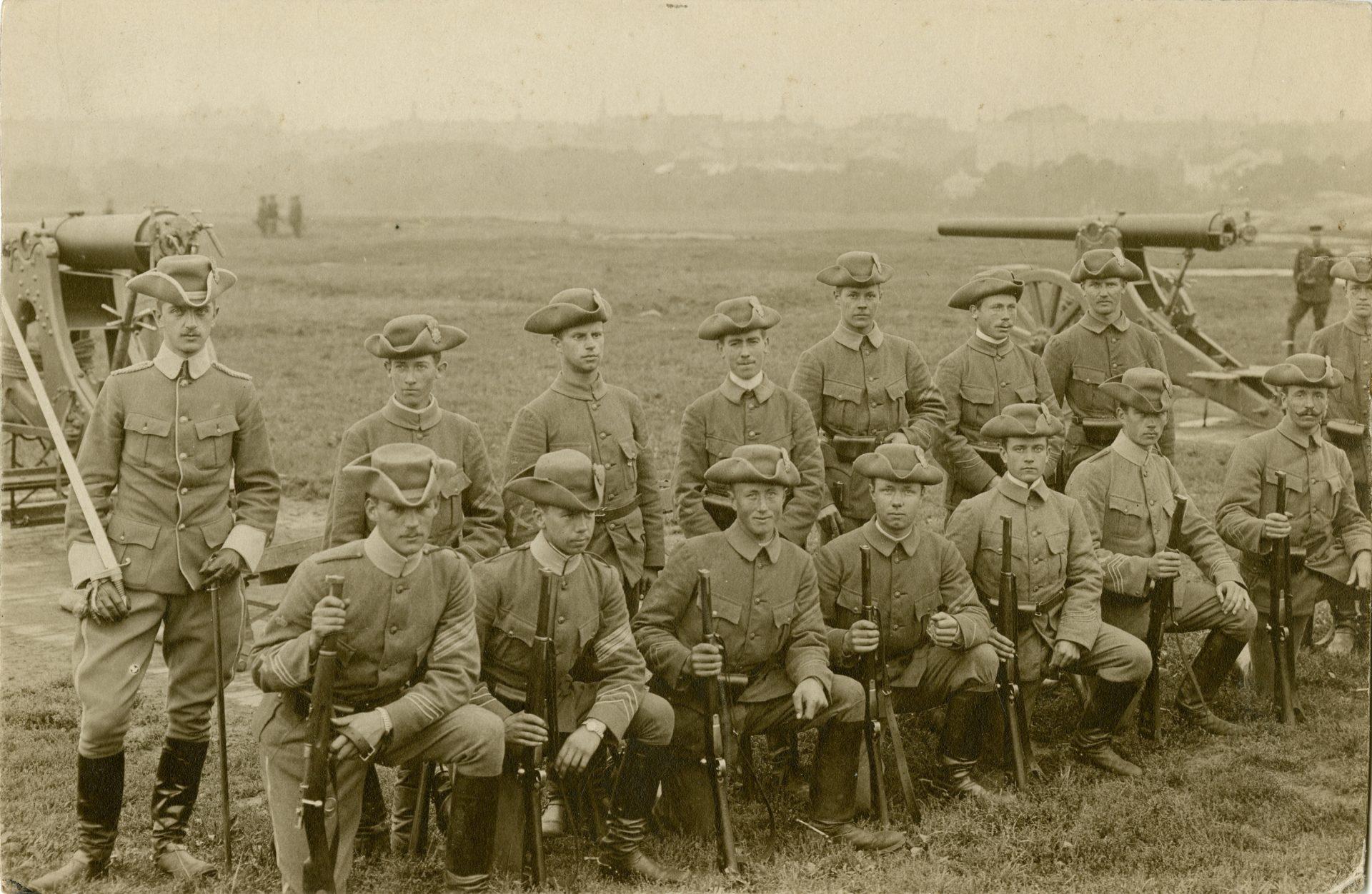 Gammalt foto på soldater med gevär i händerna framför en kanon
