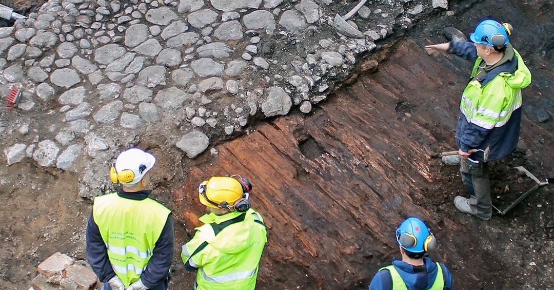 Fyra personer i plasthjälmar och gula västar som tittar ner på en utgrävning.