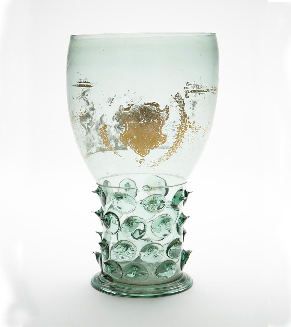 Ett grönt glas med gulddekor.