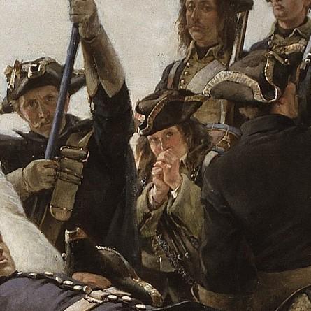 En ung soldat som blåser i händerna för att värma sig.