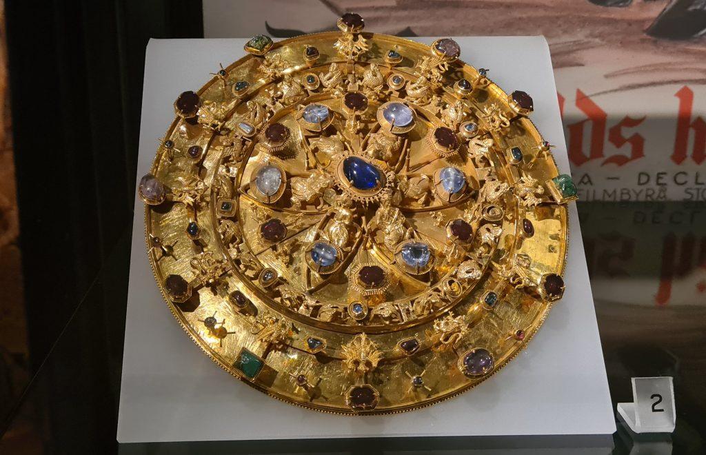 En mycket grann skiva av guld med små figurer och ädelstenar.