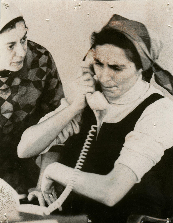 En kvinna med bekymrat ansiktsuttryck pratar i telefon. En annan kvinna tittar på henne.